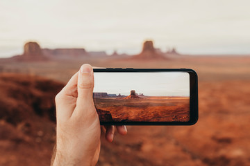 hand holding a phone while taking a photo of typical Utah Landscape