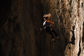 Woman rock climber falls on rope against a dark background.
