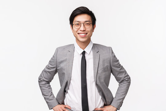 Lets earn some money. Handsome confident and smart asian businessman in suit and tie, standing in ready, determined pose, smiling upbeat, assured he will get deal, white background