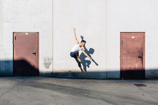 A dancer dancing in front of a concrete wall