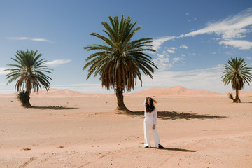 Three palms and a person in the desert