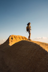 Young woman doing hiking with a backpack on top of a big rock, during sunrise