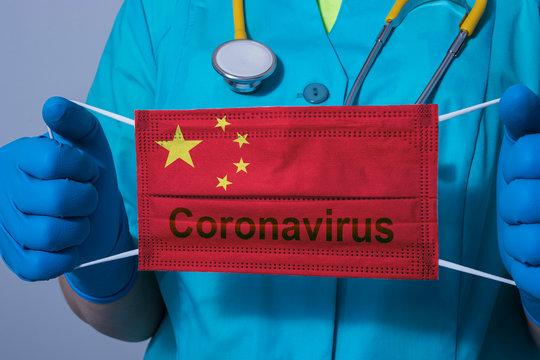 """Doctor in a protective suit and blue gloves holds a medical mask with the flag of China and the word """"Coronavirus"""""""