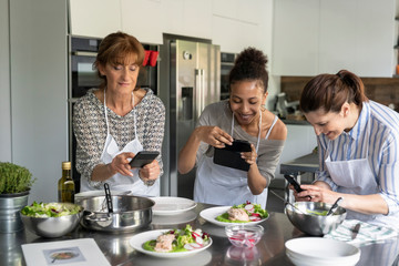 Women taking pictures at the food in kitchen class
