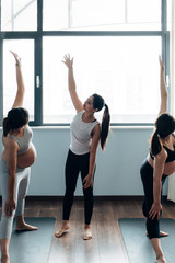 Prenatal yoga class, pregnant women doing yoga with instructor in class