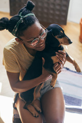 Woman spending time with her small black dog indoors