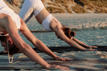 Couple in downward facing dog pose on beach