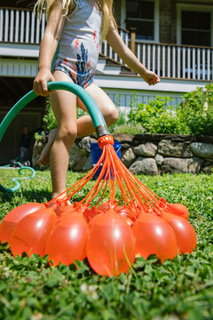 Young Girl Inflating Red Water Balloons in Backyard with Garden Hose