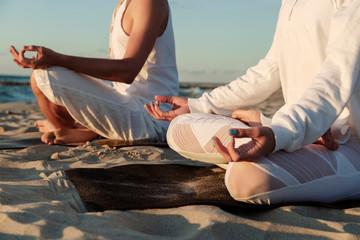 Crop couple meditating on beach