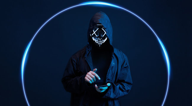Dangerous hooded hacker in mask with smartphone in his hand. Internet, cyber crime, cyber attack, system breaking and malware concept. Anonymous. Dark background.