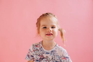 Funny little girl studio portrait on pink background