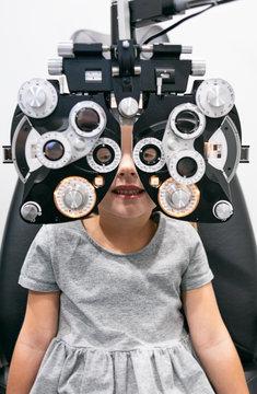 Girl looking through phoropter during eye examination