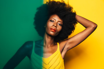 Beautiful Afro Woman posing over yellow background with green gel