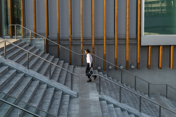 Young businesswoman running upstairs in city