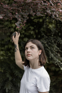 portrait of young woman reaching up into tree