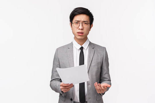 Waist-up portrait of skeptical, serious-looking asian businessman scolding employee for strange bad report, holding documents looking at camera frustrated and confused, white background