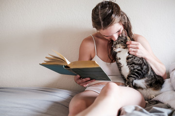 Beautiful Woman Reading a Book on Bed With Her Cat