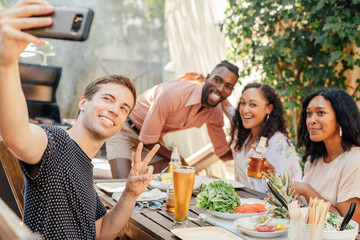 Man Takes Selfie at BBQ with Friend