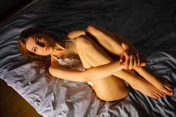 woman lying on bed clasping her legs