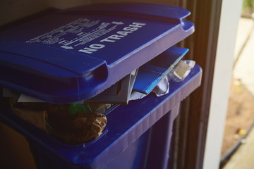 Blue recycling bin full of garbage