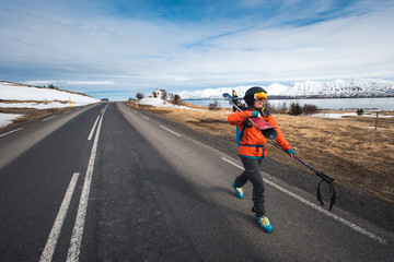 A woman walking along a paved road with skis in Iceland