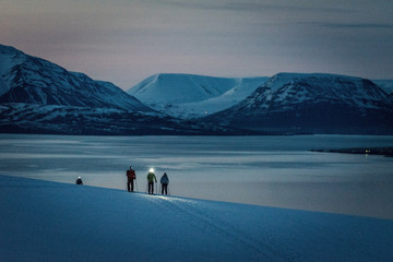 A group of 3 people skis at sunrise with ocean and mountains behind