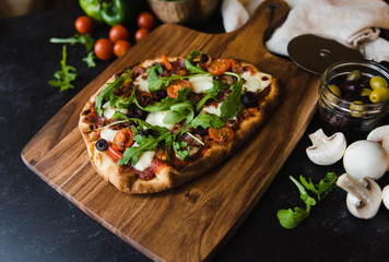 Close up of handmade pizza on wooden board with ingredients around it.