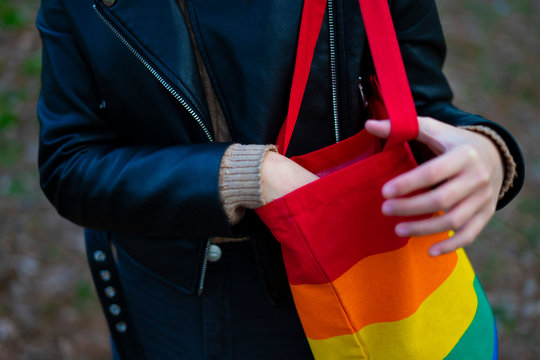 Lesbian woman catching something from her pride bag.