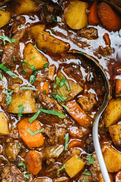 Beef stew closeup with serving spoon