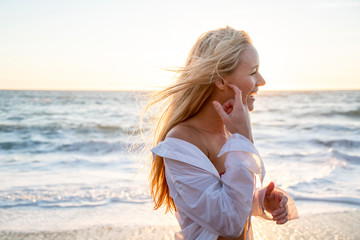 Teenage girl laughing on beach at sunset