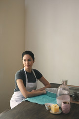 Thoughtful woman in apron sitting with containers and ingredients for preparing food at home