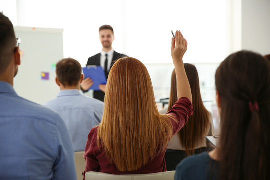 Young woman raising hand to ask question at business training indoors, back view