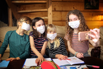 children take pictures wearing masks locked in their homes by a coronavirus pandemic