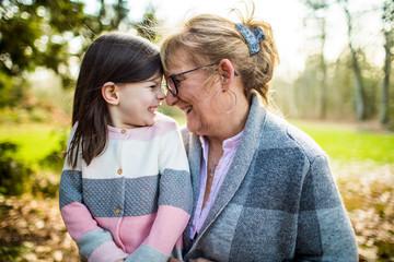 Cute girl smiling at grandma in outdoor setting.
