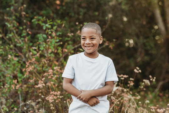 Close up portrait of young school-aged confident boy smiling outside
