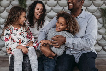 Lifestyle image of happy family tickling each other and laughing while