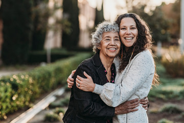 Portrait of active senior grandmother and adult daughter smiling