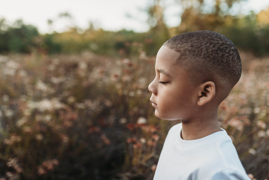 Side view of boy with eyes closed standing in field
