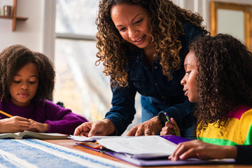 Mature woman assisting daughters studying at table in living room