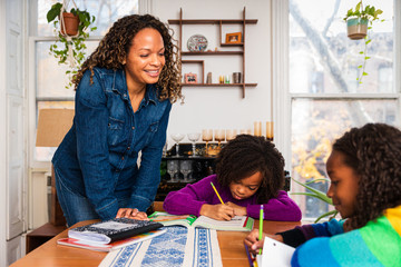 Smiling mother assisting daughters in studies at home