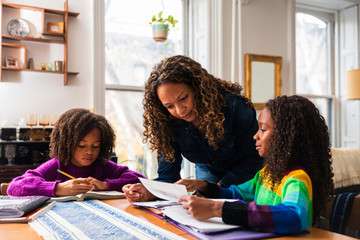 Mother assisting daughters studying at table in living room