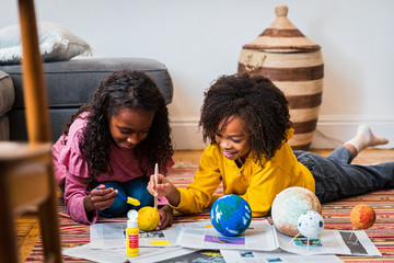 Sisters painting sphere while making solar system at home