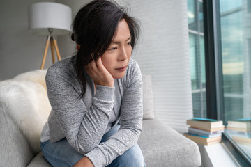 Sad Asian mature woman lonely at home self isolation quarantine for COVID-19 Coronavirus social distancing prevention. Mental health, anxiety depressed thinking senior chinese lady.