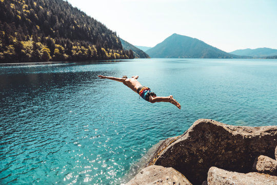Young man jumping into alpine lake in front of mountains