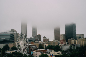 city with ferris wheel and large buildings disappearing into clouds