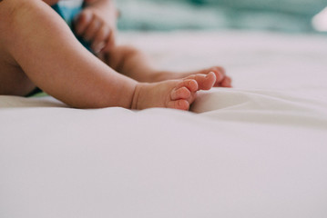 Babies feet sit on a white bedsheet