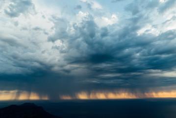 rainy storm clouds approach coastline as sun sets behind
