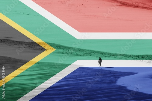A South African flag with a women walking on a beach in the background.