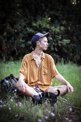 Foto op Plexiglas Centraal Europa handsome mixed race person in baseball cap sits in green summer grass