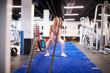A woman exercising with battle ropes on the turf at the gym.
